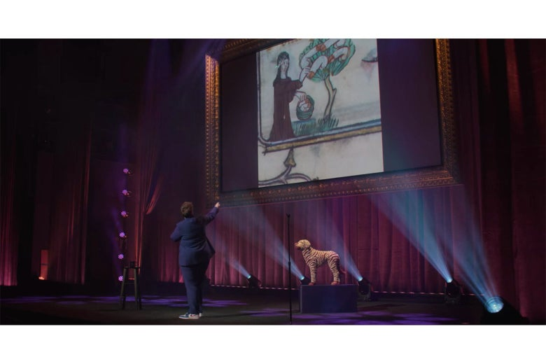 Hannah Gadsby on stage, in front of a detail from an illuminated manuscript showing a nun picking penises from a penis tree.