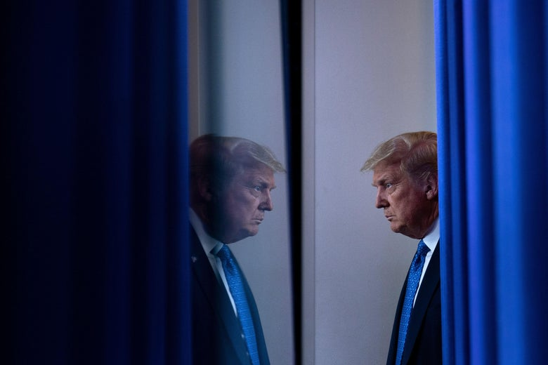 President Donald Trump appears to look at himself in a mirror.
