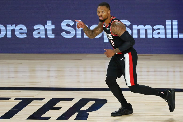 Damian Lillard pointing as he runs across the court