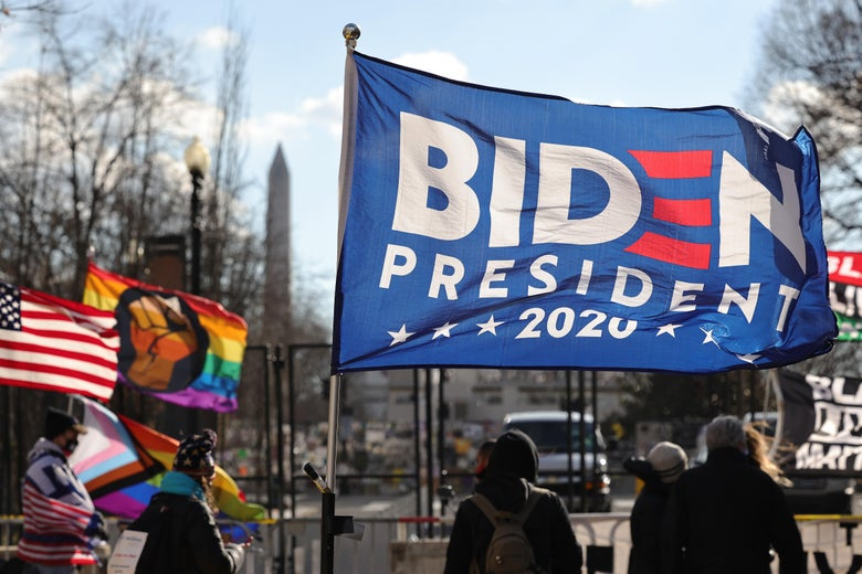 A Biden flag waves in the wind, with rainbow flags in the background