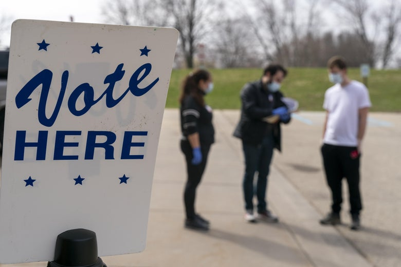 """Three people wearing surgical masks and gloves stand near a sign that says, """"Vote HERE."""""""