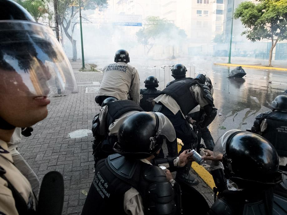 Members of the National Bolivarian Guard fire tear gas to disperse protesters during an anti-government demonstration in the Altamira neighborhood of Caracas, Venezuela, on February 19, 2014.