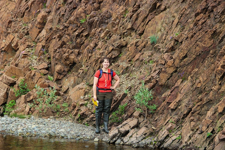 Woman wearing a red shirt standing next to a rocky cliff face near a stream of water.