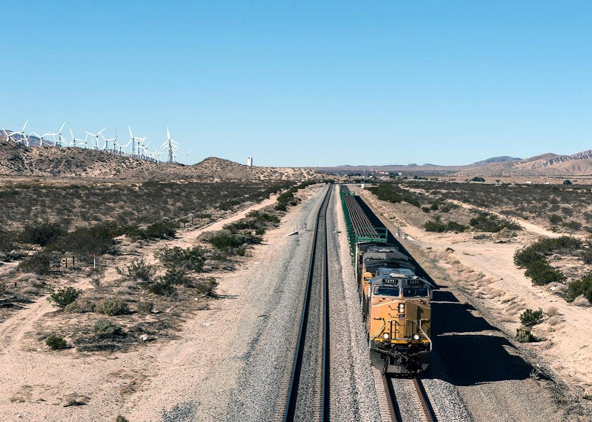 A long freight train approaches between a wind-turbine farm and