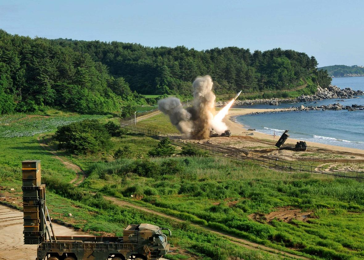 In this handout photo released by the United States Forces Korea, U.S. M270 Multiple Launch Rocket System (R) firing an MGM-140 Army Tactical Missile