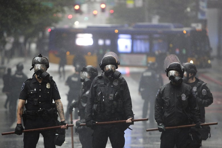 Police in gas masks stand in the street after protests in Seattle, Washington on May 30, 2020.