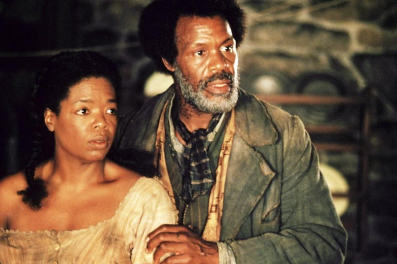 Danny Glover puts his hand on Oprah's arm as the two stare at something off camera.