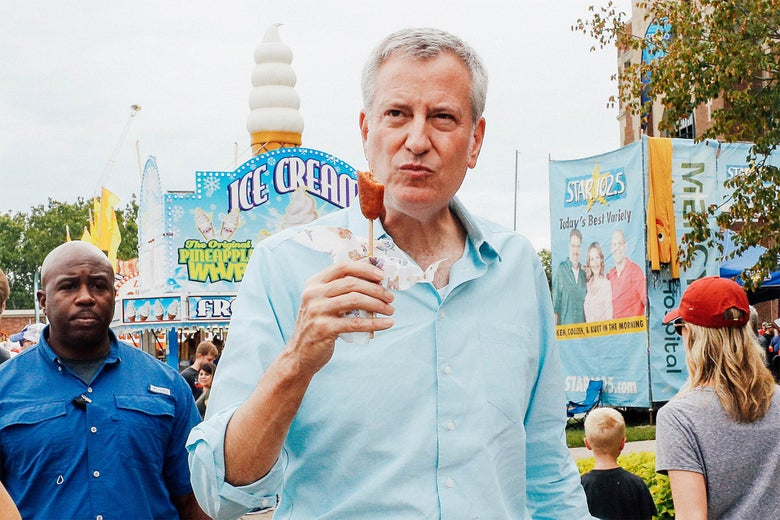 New York City Mayor Bill de Blasio, a Democratic 2020 U.S. presidential candidate, eats a corn dog at the Iowa State Fair in Des Moines on Sunday.