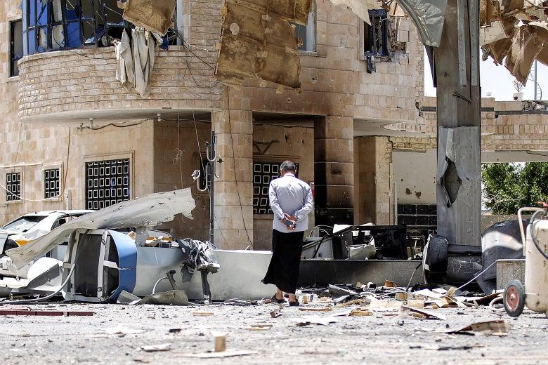 A Yemeni man walks through the rubble and debris.