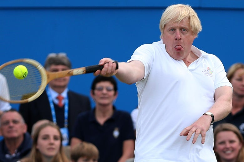 Boris Johnson sticks his tongue out as he hits a tennis ball while spectators watch.