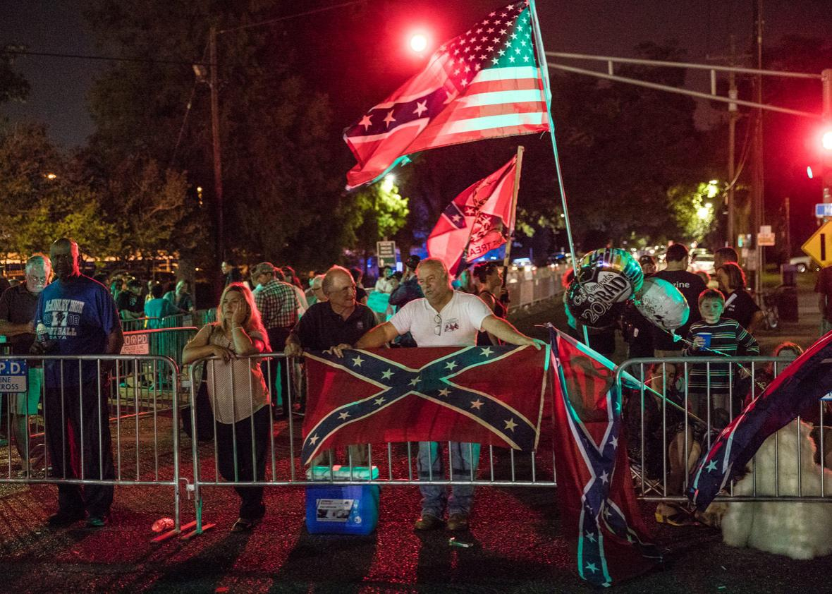 Protestors hold flags across the street from the G.T. Beauregard Monument before its removal on May 16, 2017 in New Orleans, Louisiana.