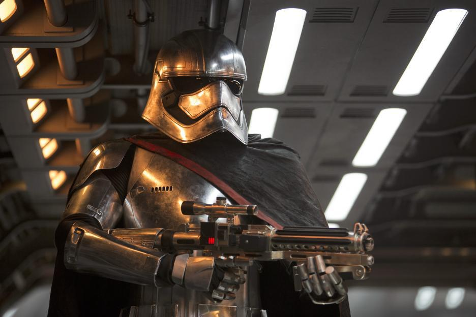 Captain Phasma wears a silver helmet that covers her face, silver armor and a black cape. She holds a large blaster.