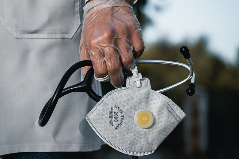 A gloved hand holds a stethoscope and mask