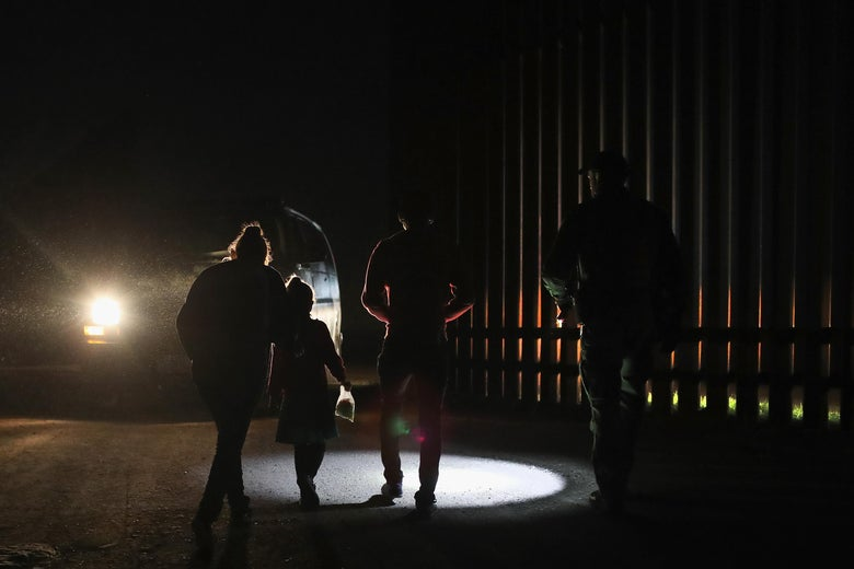 A Honduran mother walks with her children next to the U.S.-Mexico border fence as they turned themselves in to Border Patrol agents on February 22, 2018 near Penitas, Texas.