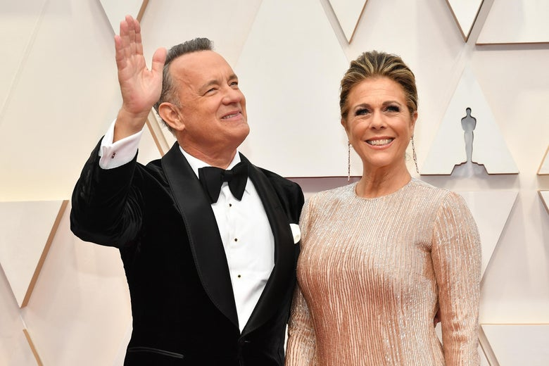 Tom Hanks, in a tuxedo, and Rita Wilson, in a beige evening gown, on the red carpet at the academy awards.