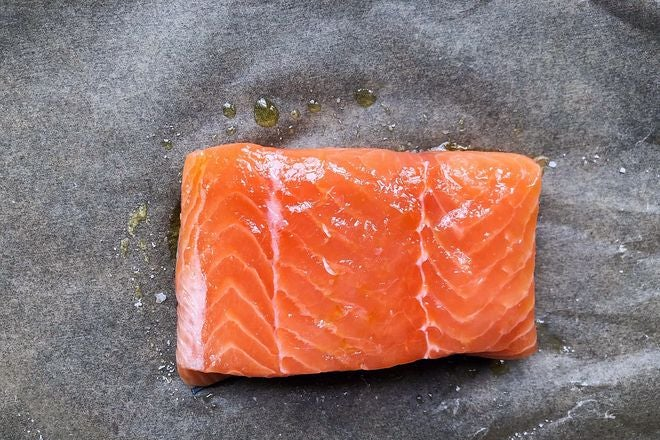 A piece of raw salmon, drizzled with oil and sprinkled with salt, on a piece of wax paper.