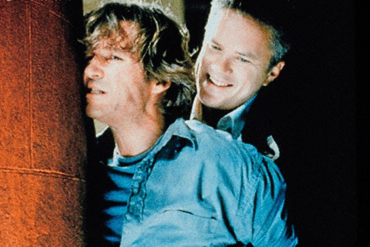 Tim Robbins smirking as he holds Jeff Bridges up against a wall, in a scene from Arlington Road.