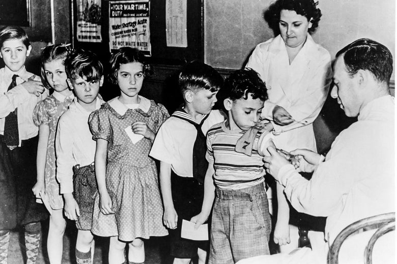 A man in a white coat administers a shot to a boy's arm. Behind the boy there is a long line of kids waiting for their shots.