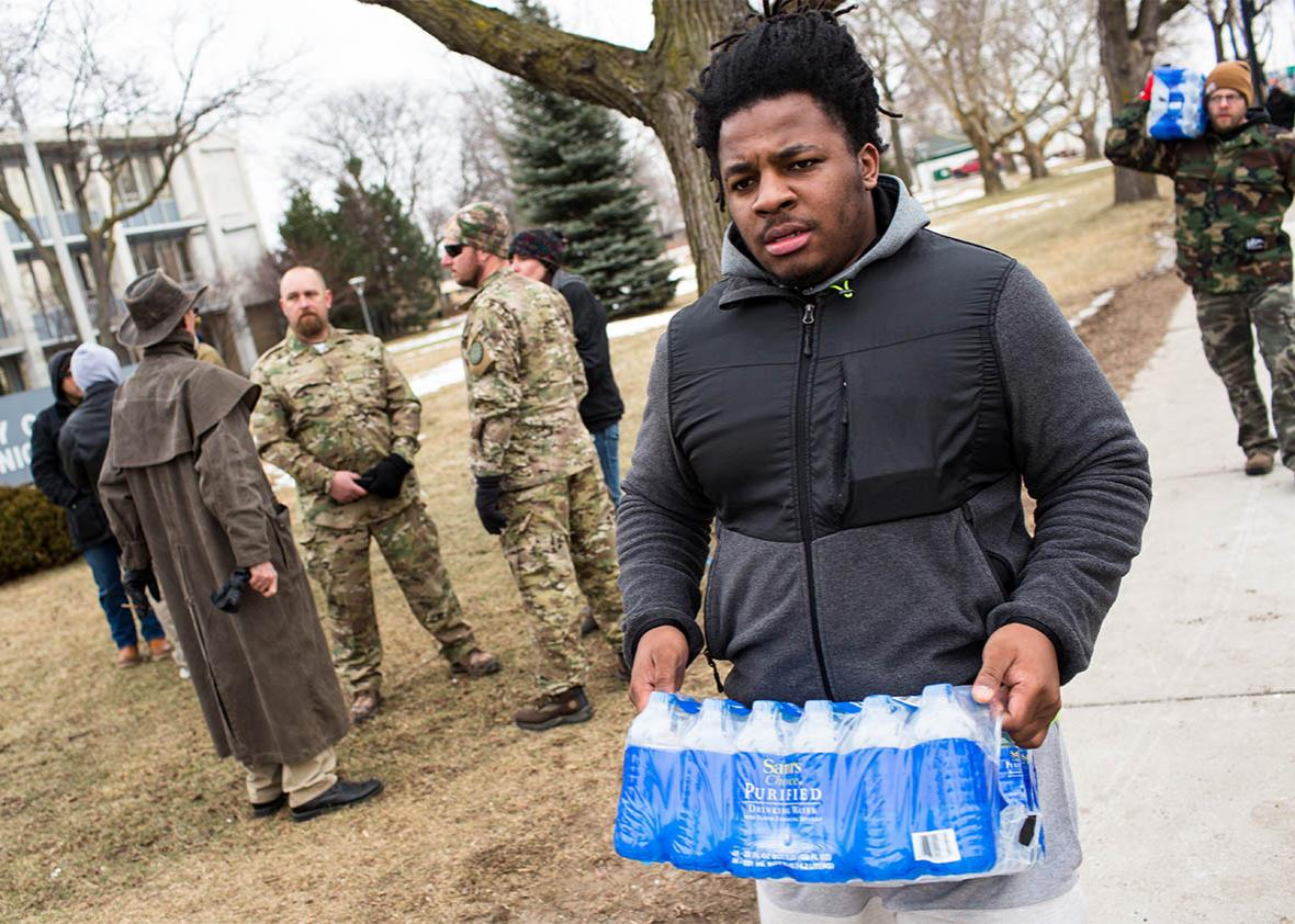 Darius Simpson, an Eastern Michigan University student from Akron, Ohio, carries water he brought to donate for Flint residents during a rally, Jan. 24, 2016, at Flint City Hall in Flint, Michigan.