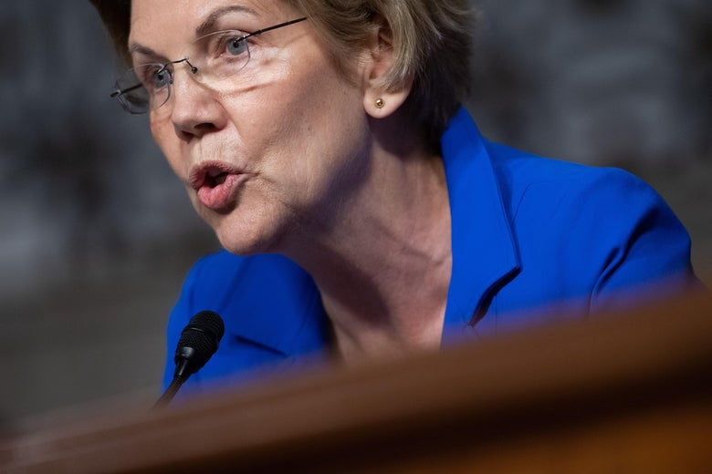 Warren speaks into a microphone at a Senate confirmation hearing