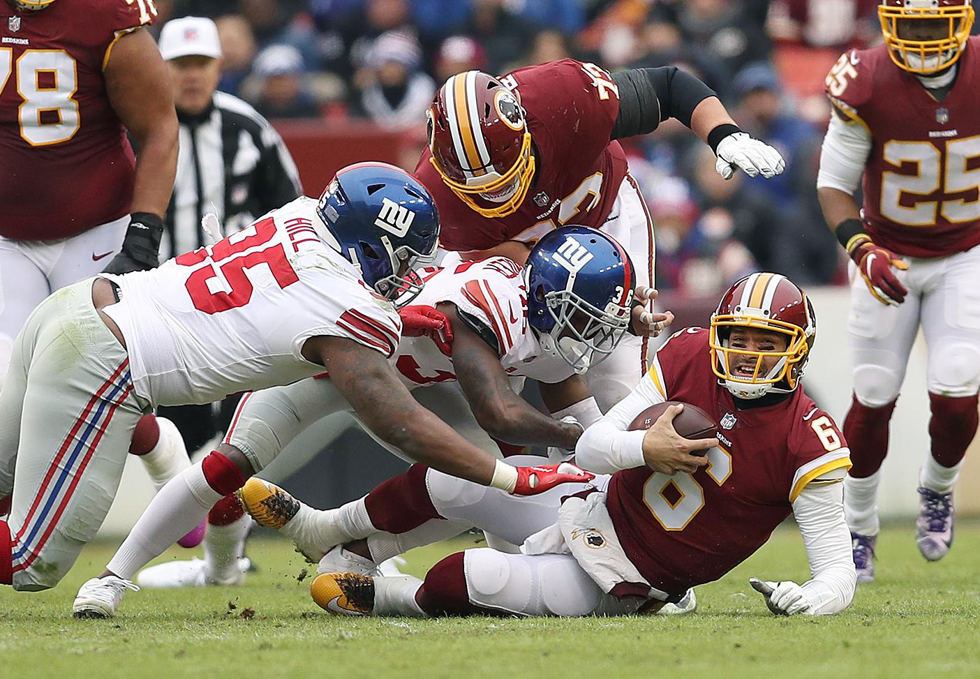 LANDOVER, MD - DECEMBER 09:Quarterback Mark Sanchez #6 of the Washington Redskins is sacked by defensive back Sean Chandler #36 and defensive end B.J. Hill #95 of the New York Giants in the first quarter at FedExField on December 9, 2018 in Landover, Maryland. (Photo by Patrick Smith/Getty Images)