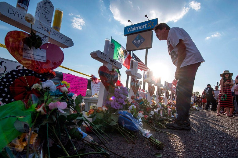 People pay their respects at a memorial of crosses and flowers honoring the shooting victims.
