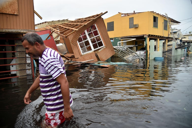 A man walks past a house laying in flood water