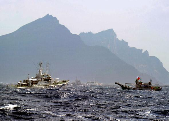 A Taiwan fishing boat (R) is blocked by a Japan Coast Guard (L) vessel near the disputed Diaoyu/Senkaku islands in the East China Sea.