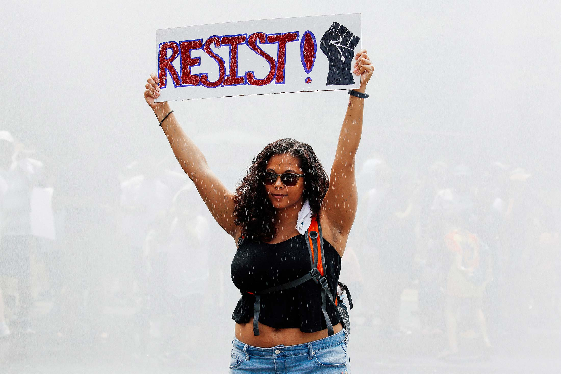 """A young woman defiantly holds up a """"RESIST!"""" sign as she stands in a spray of water from a fire truck during a protest."""