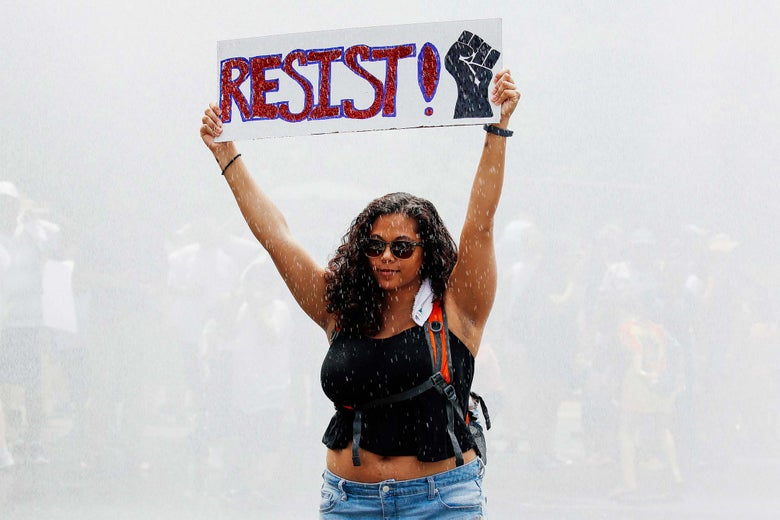 "A young woman defiantly holds up a ""RESIST!"" sign as she stands in a spray of water from a fire truck during a protest."