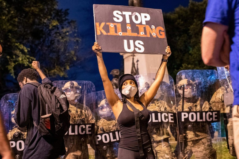 "A demonstrator holds a sign reading ""Stop Killing Us"" in front of a police line outside of the White House on May 30, 2020 in Washington, D.C."