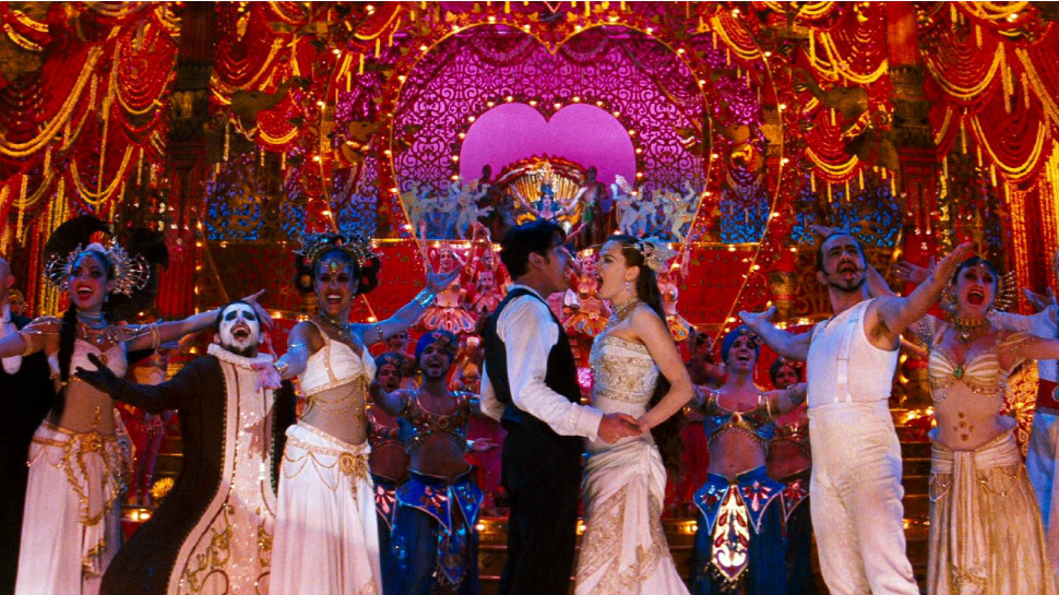 Ewan McGregor and Nicole Kidman sing and embrace inside among colorful cabaret performers.