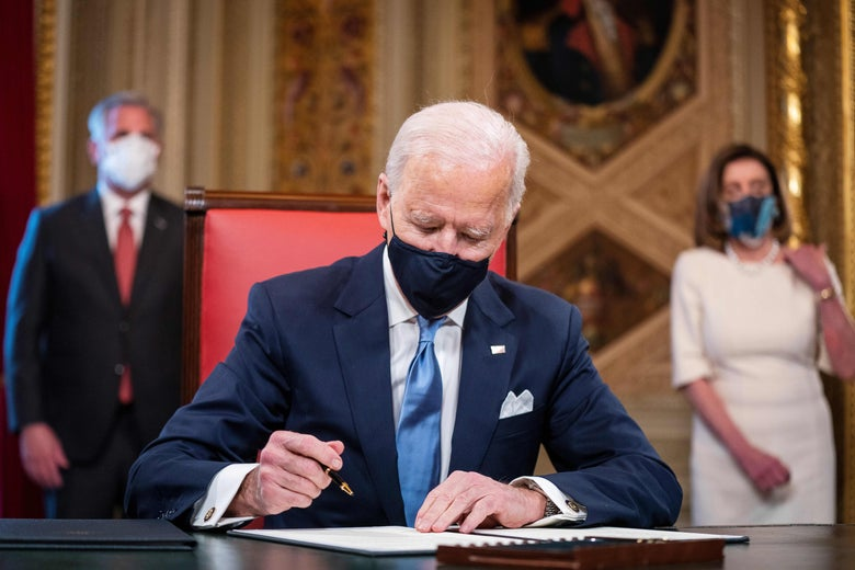 Biden in a mask signing a document