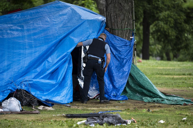 A man in a police uniform peers behind a tarp over a tent.