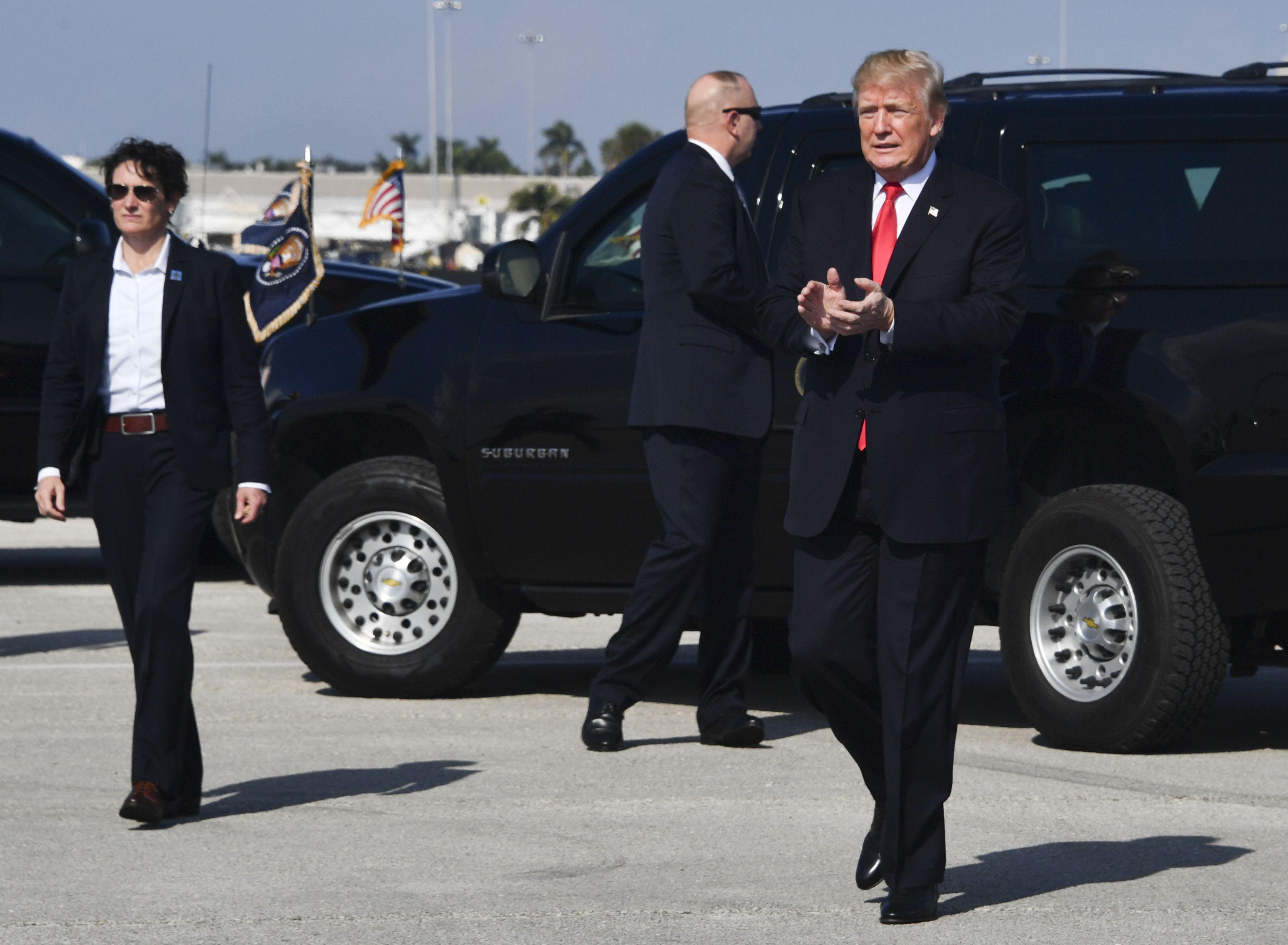 United States President Donald J. Trump walks to greet supporters during his arrival at Palm Beach International Airport in Palm Beach, Florida on December 22, 2017.  / AFP PHOTO / Nicholas Kamm