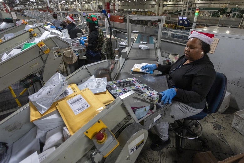 U.S. Postal Service workers scan parcels and pass them along a conveyor belt at the Los Angeles Processing and Distribution Center.