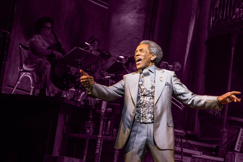 André De Shields singing onstage with his arms outstretched