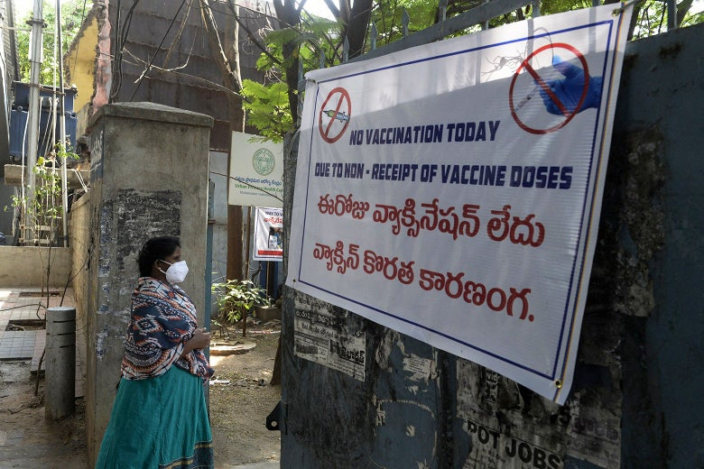 """A woman walks past a sign reading """"No vaccination today due to non-receipt of vaccine dose."""""""