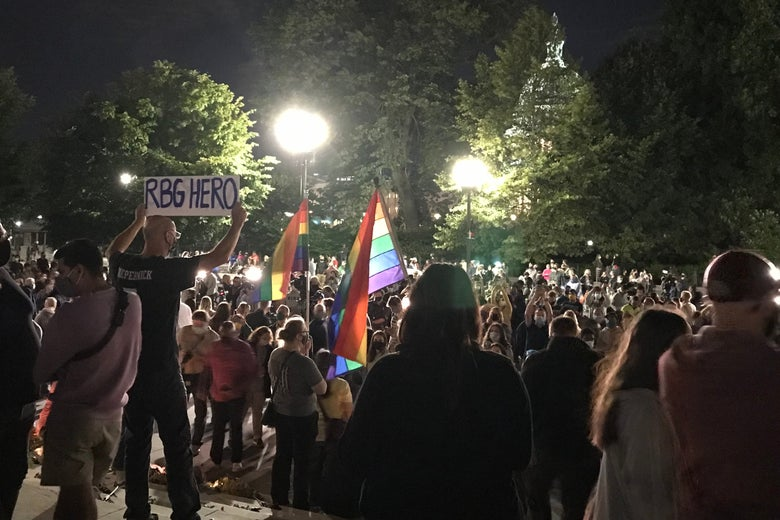 """A man holds a sign reading """"RBG Hero"""" amid a large crowd with waving rainbow flags and the Capitol in the background."""
