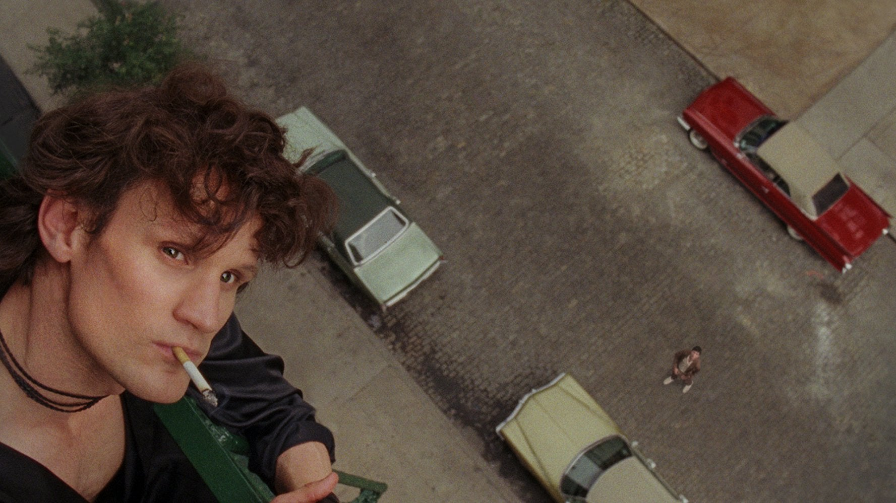 Matt Smith, a young man with curly brown hair and a square jaw, plays Robert Mapplethorpe in the biopic Mapplethorpe. He wears a black silk robe and smoke a cigarette on his fire escape, looking up. Cars move on the street below him.