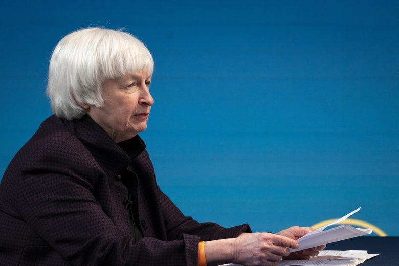 Treasury Secretary Janet Yellen siting at a table holding papers.