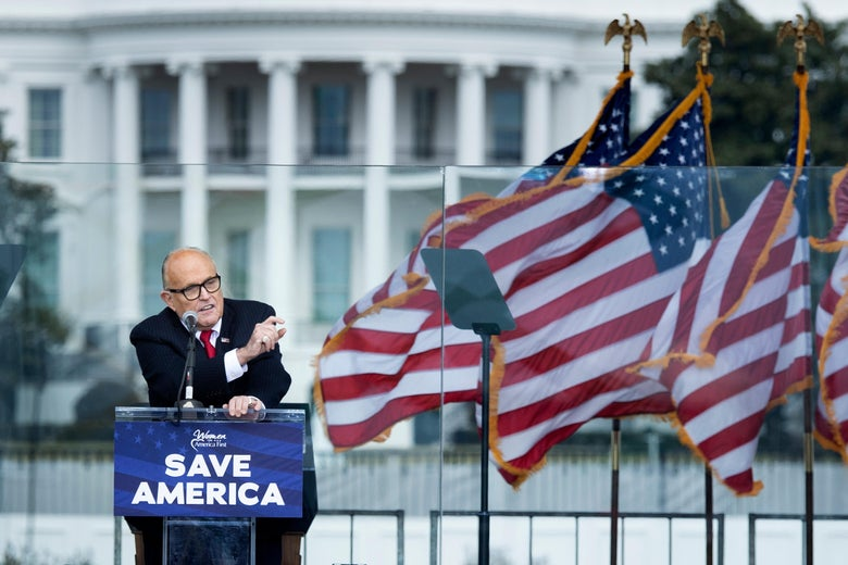 """Rudy Giuliani speaks at a podium that says """"Save America"""" with American flags waving beside him. The White House can be seen in the distance behind Giuliani."""