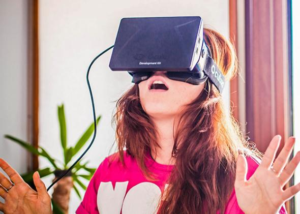 A young woman uses the Oculus Rift.