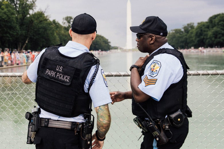 Two police officers chat in front of a chain-link fence with the reflecting pool and Washington Monument behind them.