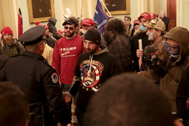A hallway in the Capitol crowded with rioters wearing Trump insignia. One rioter wearing a black QAnon shirt stares down a police officer.
