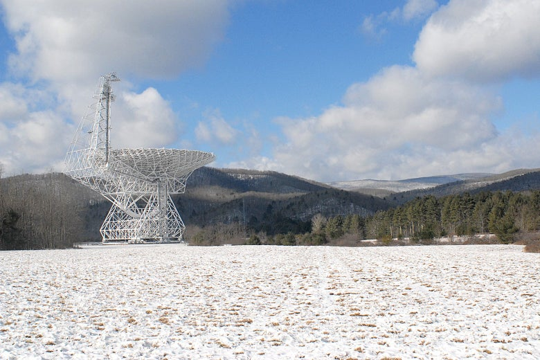 A large telescope in the middle of a field covered in light snow.