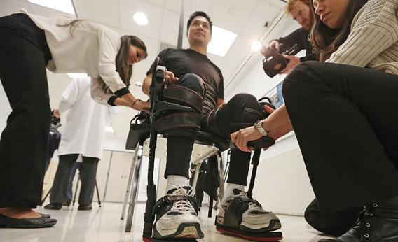 Robert Woo is outfitted with an exoskeleton device to walk in made by Ekso Bionics.