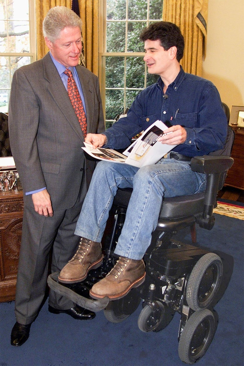 Dean Kamen sits in an iBot wheelchair in the Oval Office while showing a binder to Bill Clinton.