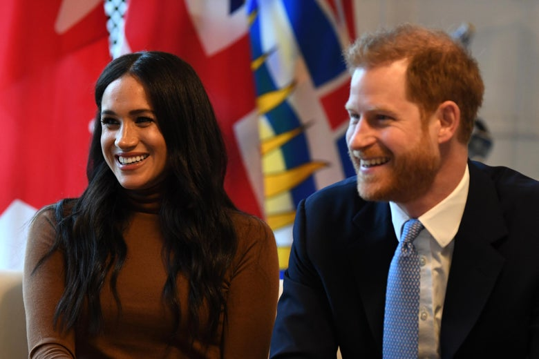 Prince Harry, wearing a navy blue suit, sits next to Meghan Markle, wearing a brown turtleneck. Both of them are smiling.