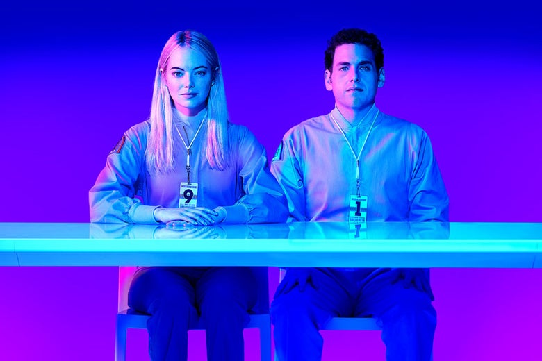 Emma Stone and Jonah Hill sit at a desk while wearing plain clothes and badges in this still from Maniac.